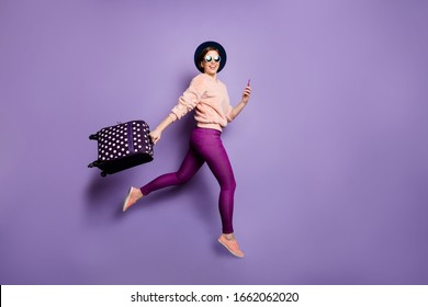 Tourism concept. Full body photo of funny lady jumping up rush airport hold telephone carry luggage wear cap glasses trendy pink pullover trousers isolated purple color background
