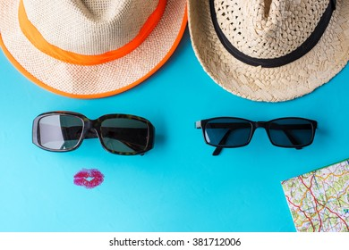 Tourism concept. He and she, a couple are ready for the road. Two hats, sunglasses and travel map against a blue background.