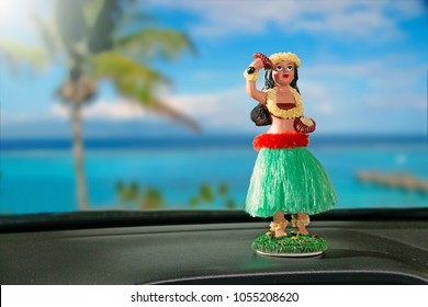 Tourism Concept. Hula dancer doll on dashboard car. The car is parking in front of the ocean. The hula dance is one of Hawaii's oldest traditions.
