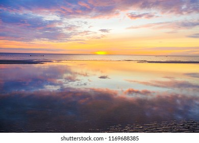 tourism concept picture of summer sunset over sand beach with reflection in Thailand
