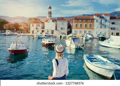 Tourism concept. Young traveling woman enjoying the view of Kastel Castle walking near the sea on Croatian coast.