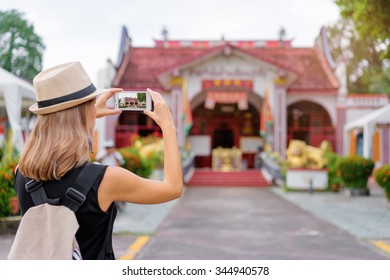 Tourism concept. Young woman with hat taking photo on smartphone while walking by the chinese town.