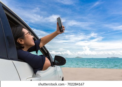 Tourism girl sit in the car and use smartphone taking selfie photo on beach with seaview