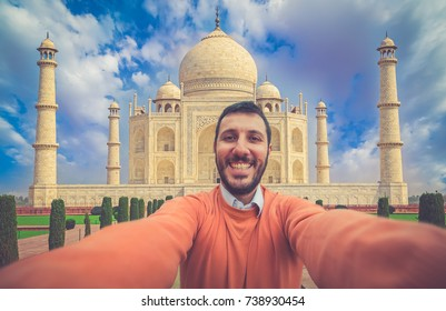 Tourism in India. Handsome smiling tourist man in holiday using mobile phone to take selfie picture at Taj Mahal, Agra, Uttar Pradesh, India.
