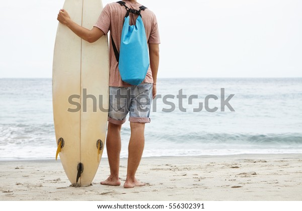 Tourism, leisure and healthy lifestyle concept. Back view of young surfer standing barefooted on sandy shore, facing vast ocean and holding his surfboard, ready to hit waves on windy summer day