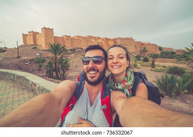 Tourism in Morocco, happy tourist take photo selfie in front of the kasbah building in moroccan berber town ouarzazate
