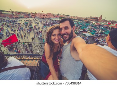 Tourism in Morocco. Happy tourists couple take selfie photo in the old main square Jamaa el-Fna market Marrakech at sunset. concept of travel, fun, discover and culture