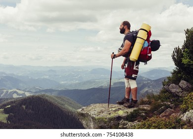 tourism, mountains, lifestyle, nature, people concept- Young man standing on top of cliff in summer mountains at sunset and enjoying view of nature