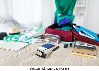 tourism, people and luggage concept - happy young woman packing travel bag at home or hotel room