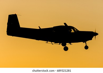 Tourism plane land at sunset after the last flight of day, before the night. Turbo propeller aircraft silhouette with orange sky as background. After a day of work, do a flight is best relax method.
