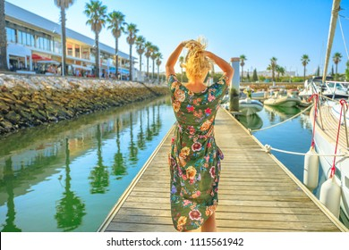 Tourism in Portugal. Lifestyle female tourist on wooden jetty at Marina de Lagos on Algarve coast, Portugal, Europe. Caucasian woman looking at the Bay of Lagos in summer holidays.