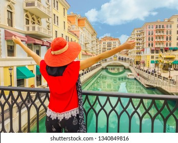 Tourism in Qatar. Woman with open arms on balcony at famous bridge reflecting on waters of canals in Venice Doha city. Caucasian tourist at Qanat Quartier in the Pearl-Qatar, Persian Gulf, Middle East