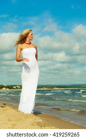 Tourism and recreation. Beauty attractive woman walking on sea edge. Female tourist resting on fresh air on seaside.