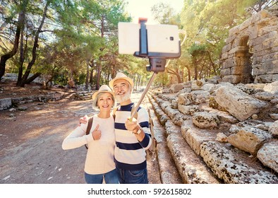 Tourism and technology. Traveling senior couple taking selfie together against ancient sightseeing background.
