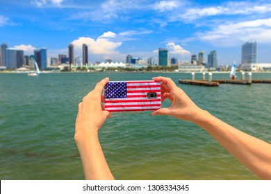 Tourism and travel in California, West Coast. Mobile phone with American flag cover taking photos of San Diego By skyline. Smartphone shoting in summer holidays from Coronado Island, USA.