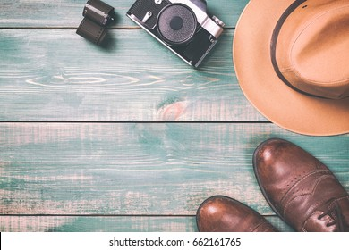 Tourism and travel concept. Vintage camera with film, brown shoes and fedora hat on green wooden background. Toned image and free space