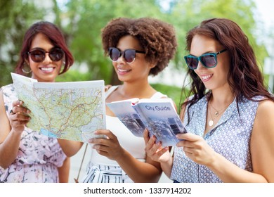 tourism, travel and friendship concept - happy tourist women or friends with map and city guide on street in summer