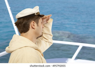 Tourism, travel and marine concept - man in captain hat looks forward