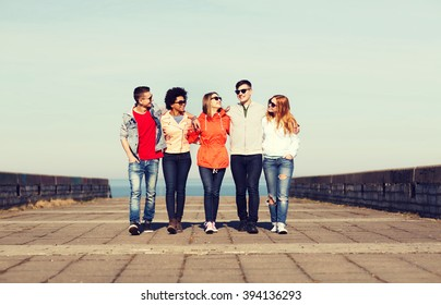 tourism, travel, people and friendship concept - group of happy teenage friends walking along city street and talking