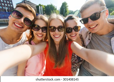 tourism, travel, people, leisure and technology concept - group of smiling teenage friends taking selfie outdoors
