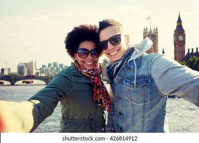 tourism, travel, people, leisure and technology concept - happy teenage international couple taking selfie over houses of parliament and thames river in london background