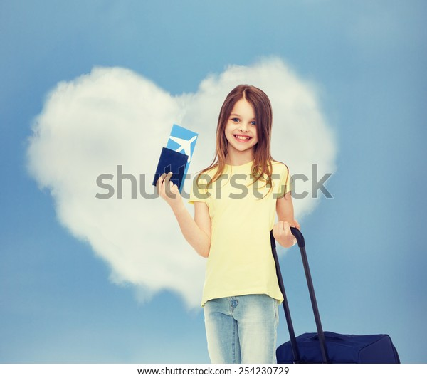 tourism, vacation, childhood and transportation concept - smiling little girl with travel bag, ticket and passport over airport background