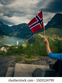 Tourism vacation and travel. Female tourist enjoying beautiful view over magical Geirangerfjorden from Flydalsjuvet viewpoint, holding norwegian flag.