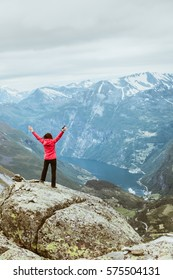 Tourism vacation and travel. Happy free tourist woman with arms raised outstretched up looking at Geirangerfjord and mountains landscape from Dalsnibba viewpoint, Norway Scandinavia.