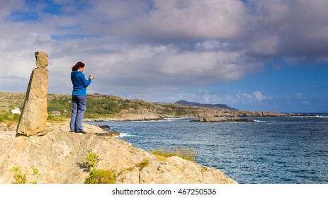 Tourism vacation and travel. Woman tourist taking photo with camera, enjoying ocean view from rocky coast, Norway Scandinavia.