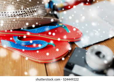 tourism, winter holidays and objects concept - close up of travel map, flip-flops, hat and camera