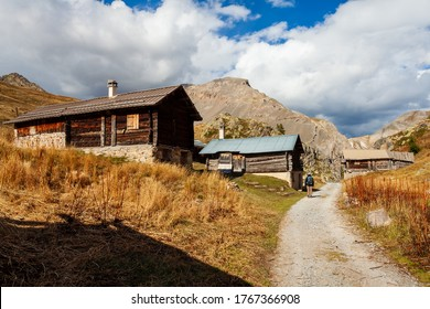 Tourist admiring huts in Alps Mountains. Houses next to path dirt road. Alpine rural rustic architecture, Arvieux, France, Europe.