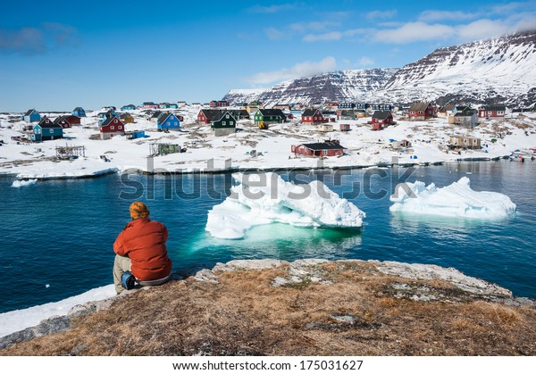Tourist admiring wonderful views of Qeqertarsuaq, small town of Greenland in early spring time