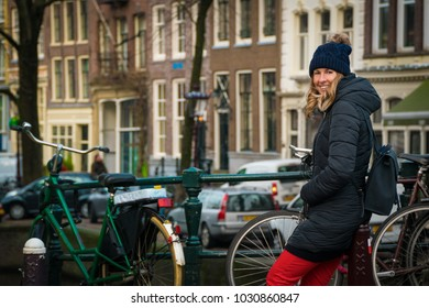 Tourist in Amsterdam - woman in her 30s waiting beside biycles on a bridge in Amsterdam