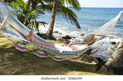 tourist asleep in hammock swinging from palm trees over the caribbean sea in corn island nicaragua central america