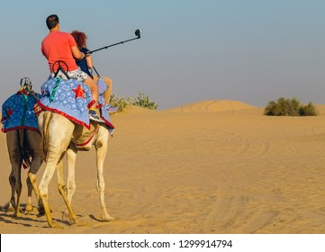 Tourist attractions sand desert safari camels using a selfie stick shot mobile phone, Tourists are taken on camel rides traditional Bedouin saddle.