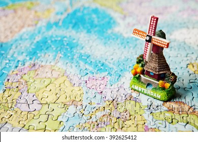 Tourist attractions and souvenir of Amsterdam windmill in the background of the world map puzzle for travelers