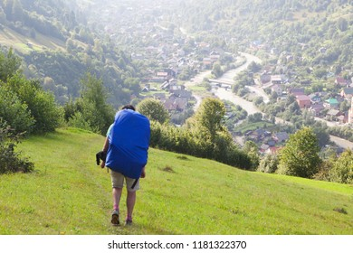 Tourist with a backpack and a dog descends into the valley