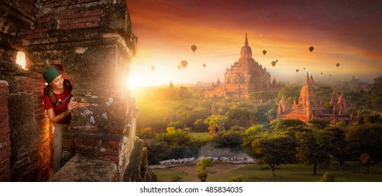 tourist with a backpack explores the ancient temple on a background of beautiful sunrise with balloons. Bagan, Myanmar.Traveling along Asia, active lifestyle concept.
