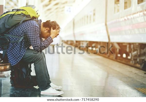 Der Tourist-Rucksack-Mann kam spät am Bahnhof an. Depressive und mühsame Reisende traurig sitzen, warten auf dem Bahnhof nach Fehlern ein Zug vergeudet Zeit auf Reisen.