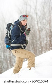 Tourist with backpack, map and navigation in the winter forest