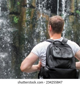 Tourist with backpack near waterfall. Space for your text.