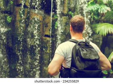 Tourist with backpack near waterfall. Vintage effect. Space for your text.