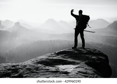 Tourist with backpack and poles in hand shadowing eyes. Sunny spring daybreak in rocky mountains. Hiker on rocky view point above misty valley. . Black and white photo