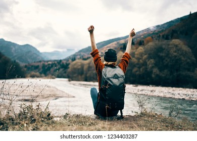 Tourist with a backpack sits near the river and looks into the mountains