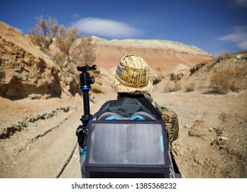 Tourist with backpack and solar panel in canyon on surreal red mountains against blue sky in the desert