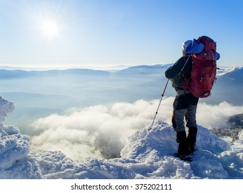 A Tourist with a backpack standing on a mountain top above the clouds and looking at the view. Direct sunlight. Clear blue sky. Winter. Mountaineering. Ukraine. Carpathians