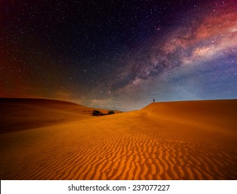 Tourist with backpack standing on top of a mountain and enjoying night sky view with stars.