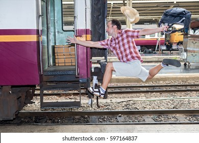 Tourist with bag running behind the train. A man runs for a wagon. Backpacker hurries for train departing from the station. Journey to the last minute.