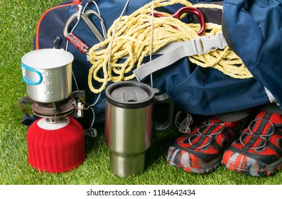 a tourist bag with shoes, on a green lawn, next to a red gas burner and a mug