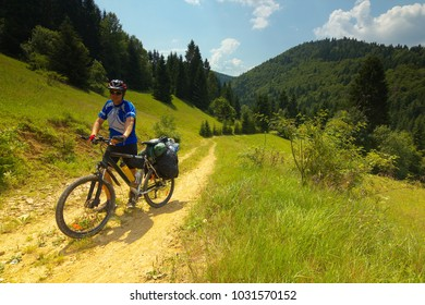 A tourist with a bicycle on a way with mountain meadows